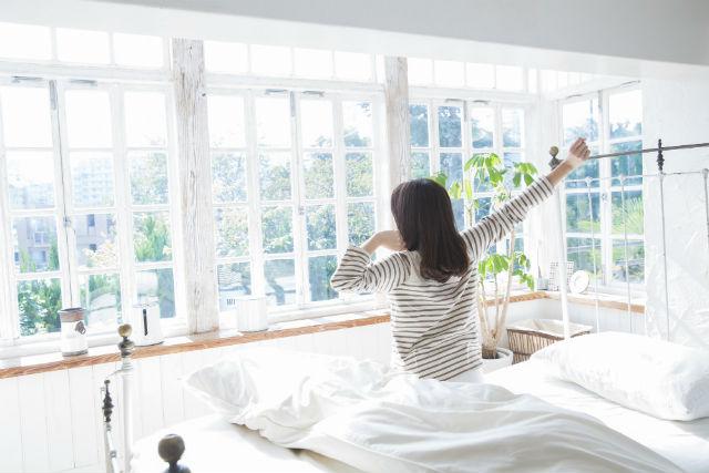 寝起きで伸びをする女性